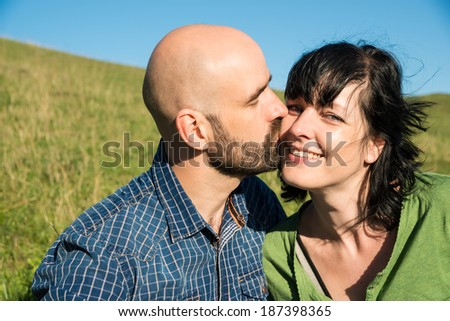 man kisses her girlfriend on cheek - stock photo