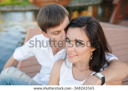 Man kissing a beautiful woman on the cheek couple. - stock photo