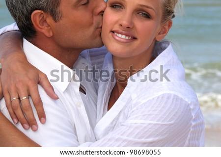 man kissing his blonde girlfriend at beach - stock photo