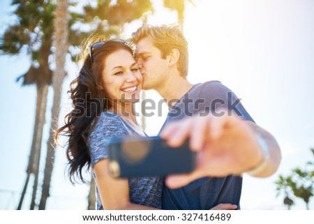 man kissing his girlfriend on the cheek for romantic selfie with lens flare and palm trees in background shot with extremely thin depth of field and lens flare effect - stock photo