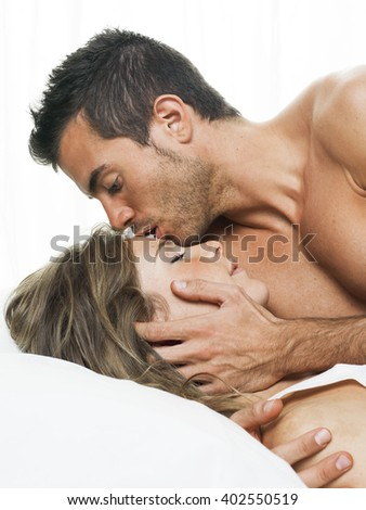 man kissing his partner sweetly in white bed - stock photo