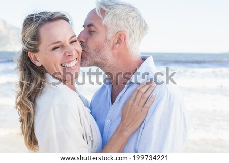 Man kissing his smiling partner on the cheek at the beach on a sunny day - stock photo