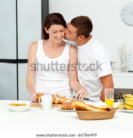 Man kissing his wife while preparing their breakfast together in the kitchen - stock photo