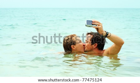 Man kissing the girl and taking the picture of them self in the sea - stock photo