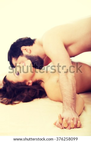 Man kissing woman in bedroom.