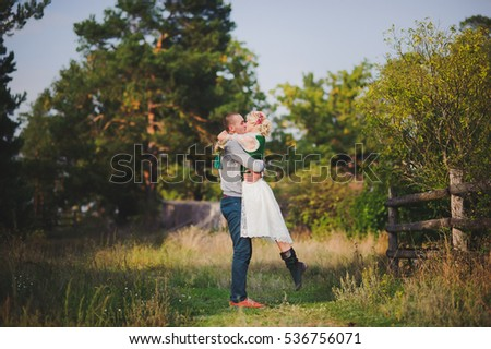 man kissing  woman on  background of wooden fence