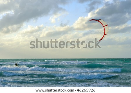 Man kite-surfing in Atlantic Ocean with dramatic weather - stock photo