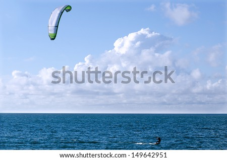 Man Kite surfing or Kite boarding, adventure surface water sport, combination of the wake boarding, windsurfing, surfing, paragliding, and gymnastics into one extreme sport - stock photo