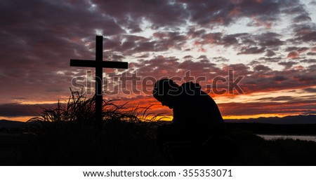 Man kneeing by a cross at first light of the day. - stock photo