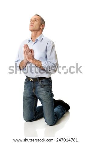 Man kneeling and praying to God. - stock photo
