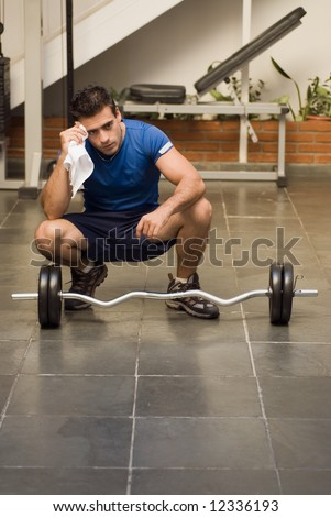 Man kneeling in front of a set of weights wiping himself off with a towel while taking a break