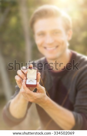 Man kneeling outside proposing with diamond ring - stock photo
