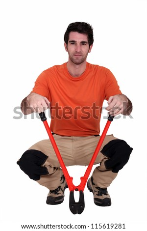 Man kneeling with bolt cutter - stock photo