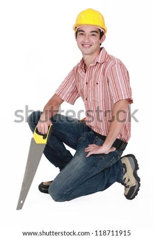 Man kneeling with saw - stock photo