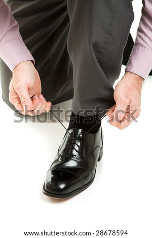 Man lacing up his shiny new black dress shoes.  Isolated on white.