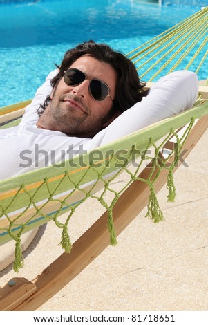 Man laid in hammock by swimming pool - stock photo