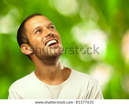 man laughing looking up against a plants background - stock photo