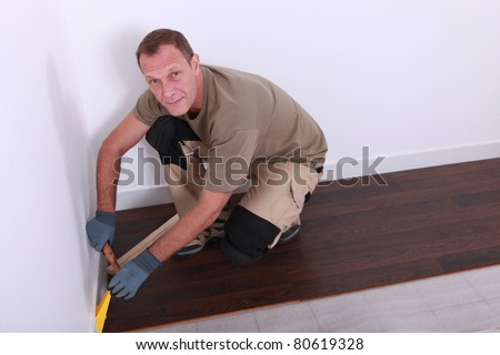 Man laying a wooden floor - stock photo