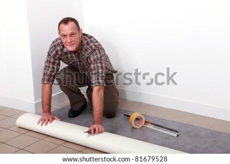 Man laying carpet - stock photo