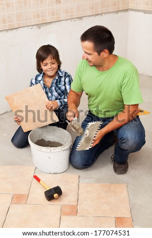 Man laying ceramic floor tiles helped by his son - parenting concept - stock photo