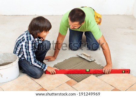 Man laying ceramic floor tiles on concrete - checking his work with a spirit level - stock photo