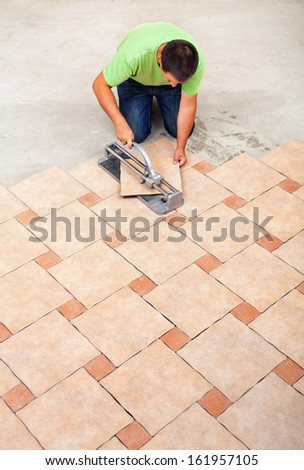 Man laying ceramic floor tiles - top view with copy space - stock photo