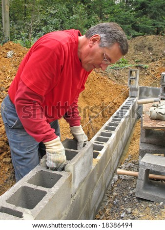 Man laying concrete block foundation wall - stock photo
