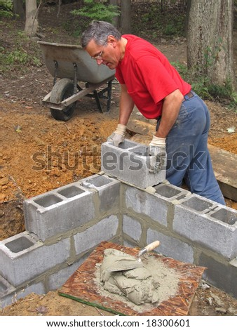 Man laying concrete block wall - stock photo