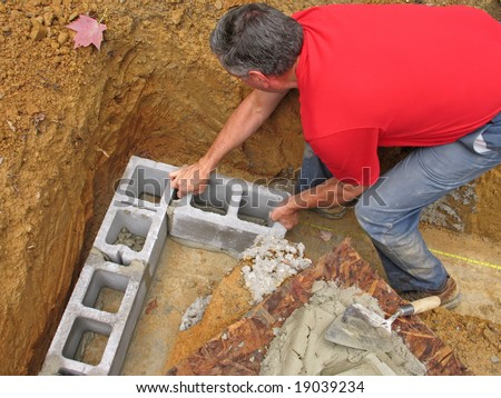 Man laying corner blocks of a foundation wall - stock photo