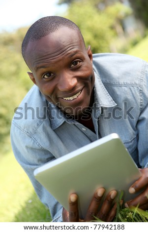Man laying down in park with electronic tablet - stock photo