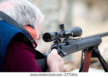 man laying down with rifle, taking aim. shot wide open, focus on front of scope