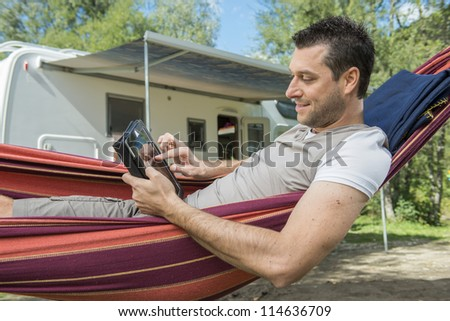 Man laying in hammock and working with tablet