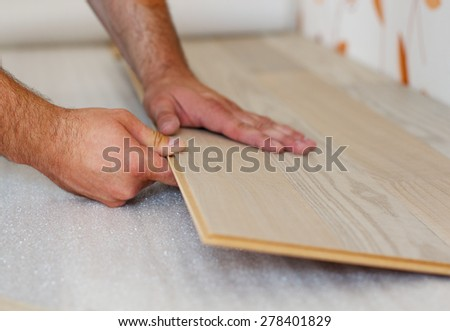 Man laying laminate flooring in a home. - stock photo