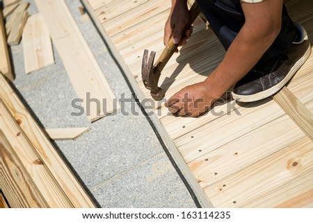 Man laying laminate flooring with tools.