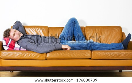 man laying on couch and resting