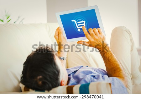 Man laying on sofa using a tablet pc against trolley - stock photo