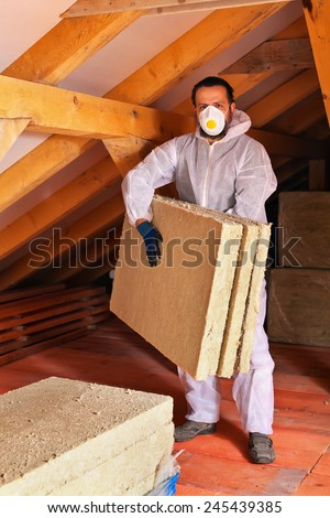 Man laying thermal insulation layer under the roof - carry the mineral wool panels - stock photo