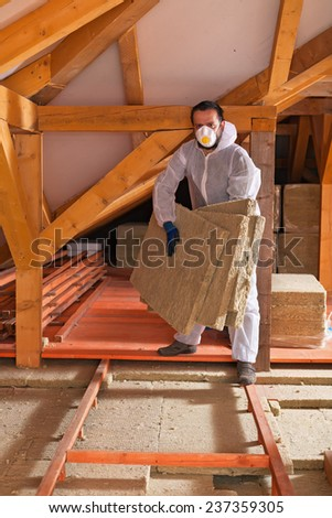 Man laying thermal insulation layer under the roof of a new building - stock photo