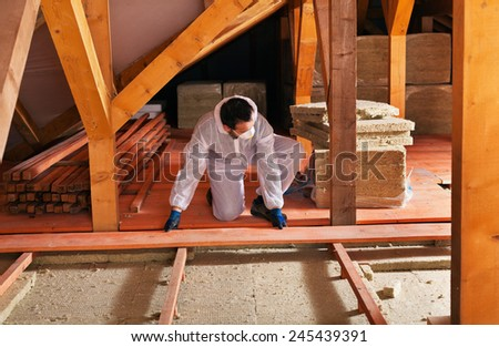 Man laying thermal insulation under the roof - installing the planking - stock photo