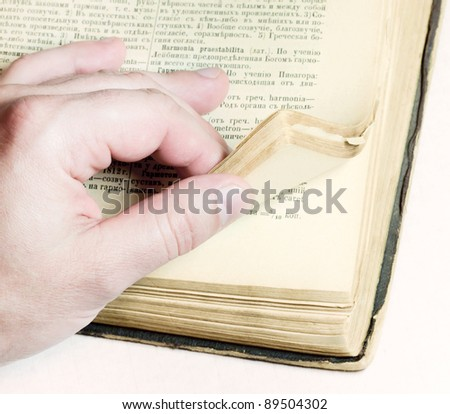 Man leafing through pages of old thick book. The old Latin-Russian dictionary of the early 20th century - stock photo