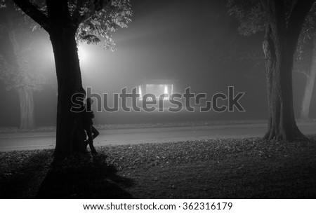 Man leaning against a tree in a foggy park. - stock photo
