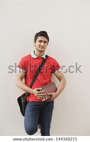 Man leaning against a wall and holding books - stock photo