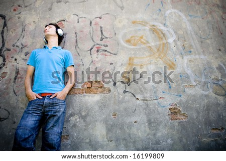 Man leaning against wall with graffiti - stock photo
