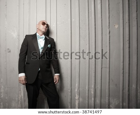 Man leaning back on a wall - stock photo