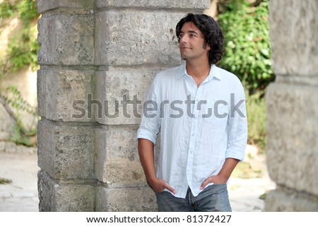 Man leaning by old stone wall - stock photo
