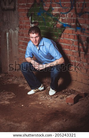 Man leaning on a brick wall in abandoned unfinished house