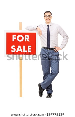 Man leaning on a for sale sign isolated on white background - stock photo