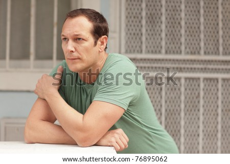 Man leaning on a ledge with his arms crossed - stock photo