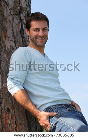 man leaning on a tree