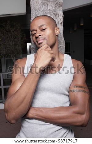 Man leaning on a tree with his hand on his chin - stock photo